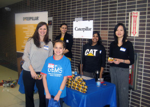 Women from Caterpillar Inc., use VEX robots and sample industry trucks to demonstrate a typical day on the job during the career fair portion of the conference.