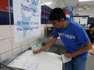 """Junior Vivek Desai signs a petition during lunch to officially name the blue cart """"Sandi's Cart."""""""
