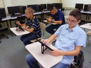 From left to right: Nick Deeke (sophomore), Jesse Hammond (sophomore), and Jack Huffman (sophomore) work on setting up their iPads in a One-to-One Program Health Science class at Fremd High School during the first day of school.