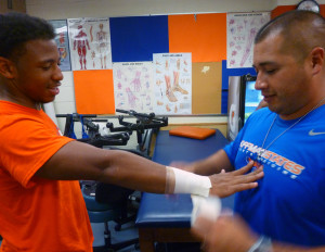 Tylic Grace (left), a senior football player at Hoffman Estates High School, gets ready for practice after the first day of school with Head Athletic Trainer Rick Bacon.