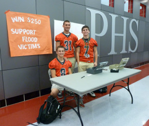(Left to Right) PHS football players Jason Lemonidis, River Crane, and EJ Miller sell raffle tickets during lunch to raise money for a high school in Colorado affected by devastating floods.