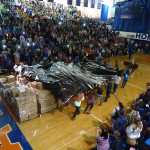 Students unveil more than 13,000 food items collected for donation during a pep assembly on Nov. 27.