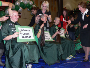 Superintendent Nancy Robb, participated by donning a green hair extension, shows students support while they shave their heads for St. Baldrick's.