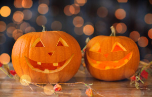 holidays, halloween party and decoration concept - close up of carved pumpkins on table
