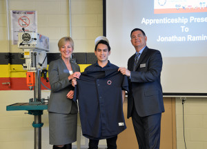 Jonathan is posing with a personalized Innovative Components shirt presented to him from Mike O'Connor, president of Innovative Components, and wears a Harper College hat presented to him by Dr. Mary Beth Ottinger, Dean of Career and Technical Programs at Harper College.